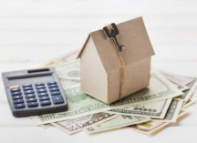 wooden home model next to money and a calculator, high-value home insurance in Plano, Texas